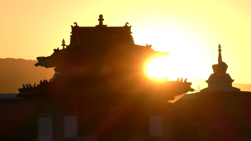 Ritual buildings of an ancient Buddhist monastery on the background of the setting sun.  Erdene Zuu monastery. Kharkhorin, Mongolia.