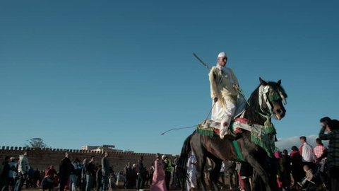 Meknes, Morocco - March 31, 2018: Moroccan tribesman competitor with rifles on horseback passing after competing in Tbourida or Fantasia competition