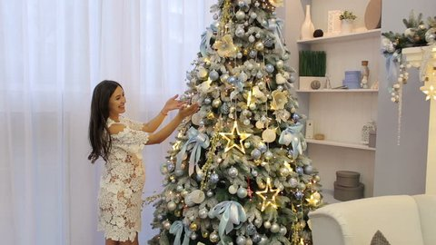 A pregnant girl in a beautiful lace white dress decorates a Christmas tree at home.