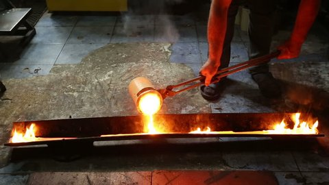 Molten silver being poured from a crucible into an ingot mold with the light coming from the molten silver. in the workshop