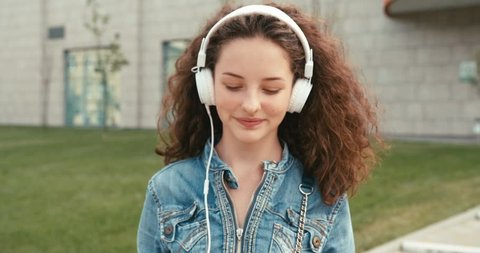 Close-up portrait of the happy emotional girl with curly dark hair and braces listening to music via white headphones and walking along the street.