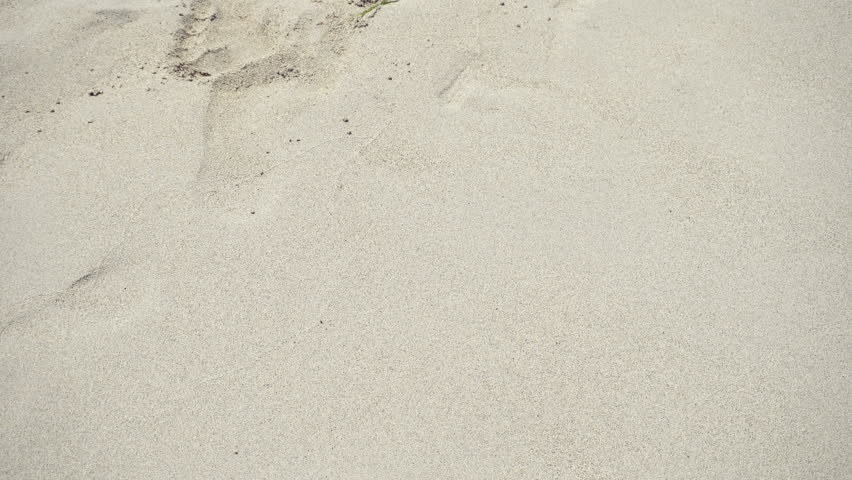 Girl draws a heart on the sea sand. The waves wash away the heart drawn on the sand.