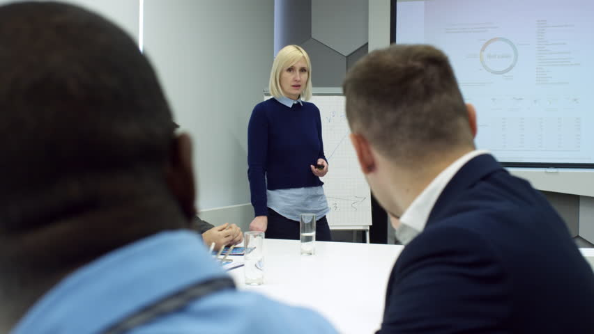 Mid-aged Caucasian businesswoman giving presentation at whiteboard and discussing plans with multiethnic group of professionals at meeting | Shutterstock HD Video #1013409638