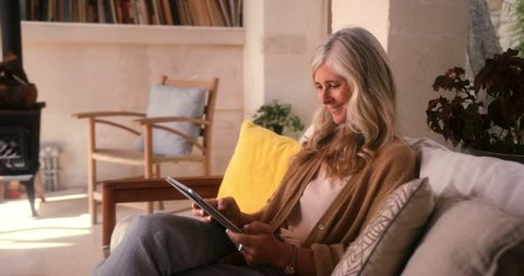 Senior woman relaxing on sofa and having fun using tablet for online browsing at home