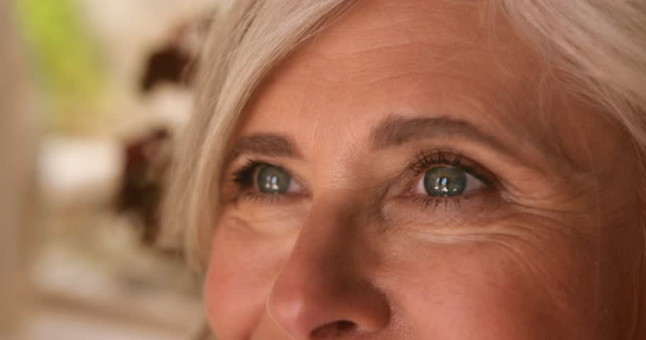 Close-up of happy mature woman's face with green eyes, gray hair and aging wrinkles