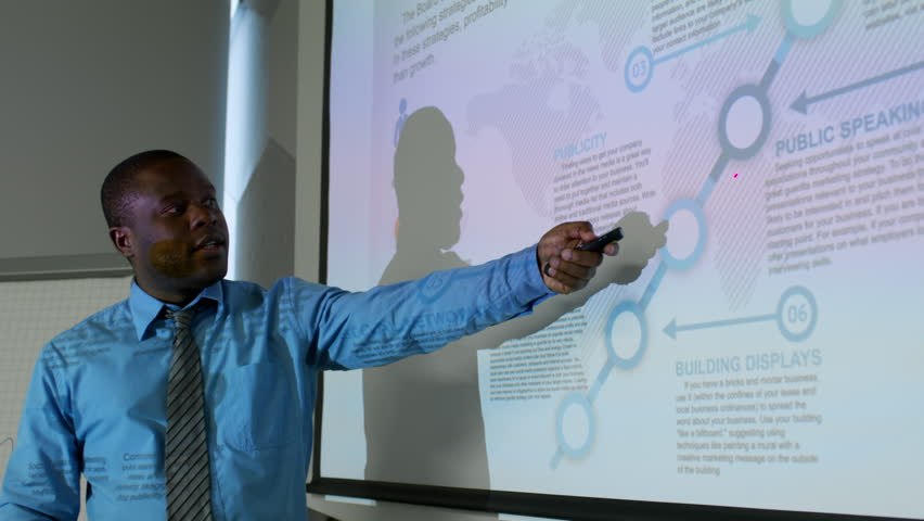 African american businessman standing at whiteboard and explaining presentation at meeting in dark office | Shutterstock HD Video #1013469548