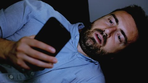 The video is about one sad man reading bad news on cellphone display at night and feeling bad.The shot is fixed on the man.