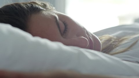 Close up face of young Caucasian woman lying and stretching on bed after waking up early in the morning
