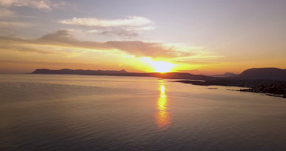 Beautiful sunrise in Agia Marina. Flying above the water with a stunning coastline view of the Crete island.   Shutterstock HD Video #1013546258
