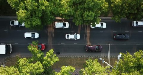 Aerial Drone Flight top down View of freeway busy city rush hour heavy traffic jam highway.  Aerial view of the vehicular intersection,  traffic at peak hour with cars on the road, fly under trees.