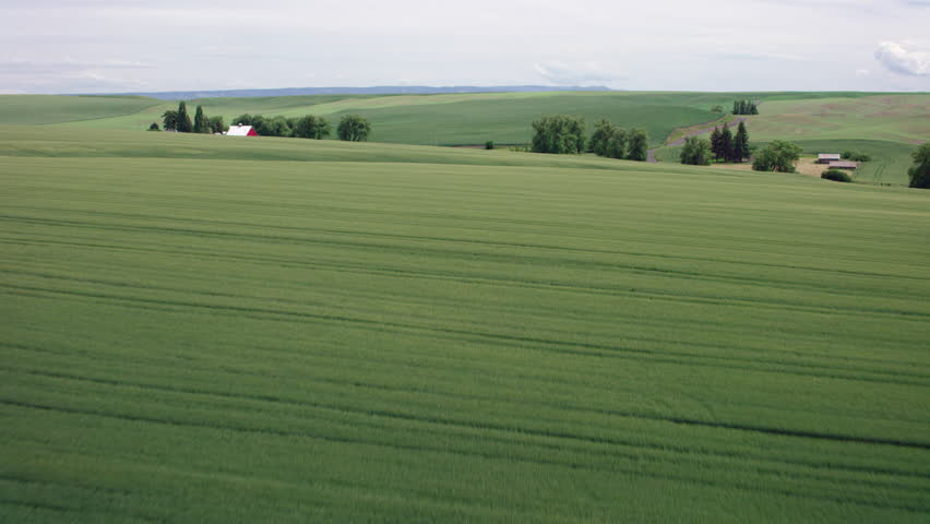Aerial showing Green Rolling Farm Fields with a Red Barn