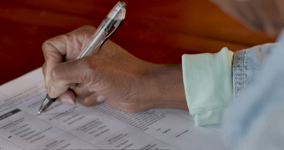 African American elderly woman voting and filling out a voter ballot during the general election - OTS