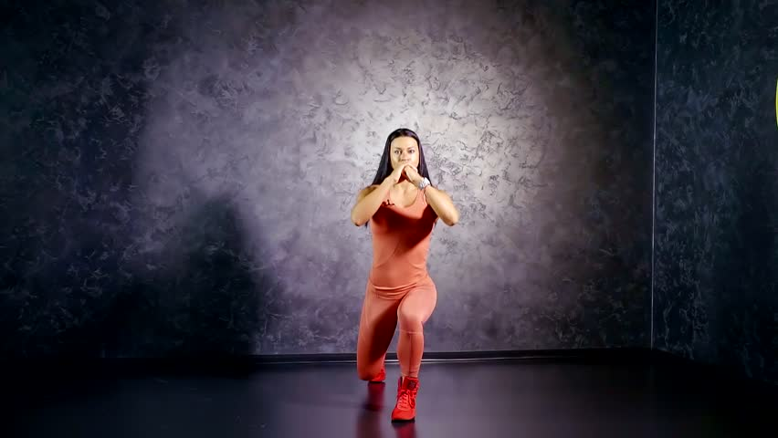 Young girl coach in a sports jumpsuit shows an exercise lunge on the spot. target muscle group quadriceps, biceps thighs and buttocks | Shutterstock HD Video #1013574548