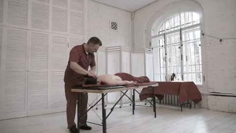 Manual therapist works with neck and shoulder. Caucasian male patient on couch against big window