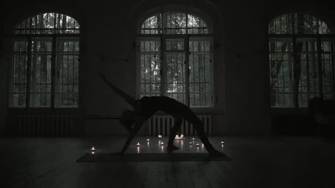 Set of yoga poses in dark room finish. Silhouette of woman against big wondow and burning candles