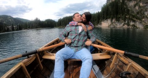 POV of a man rowing a wooden boat rowing in the middle of the lake and watching his wife smile and screams of happiness; in the background a beautiful landscape.