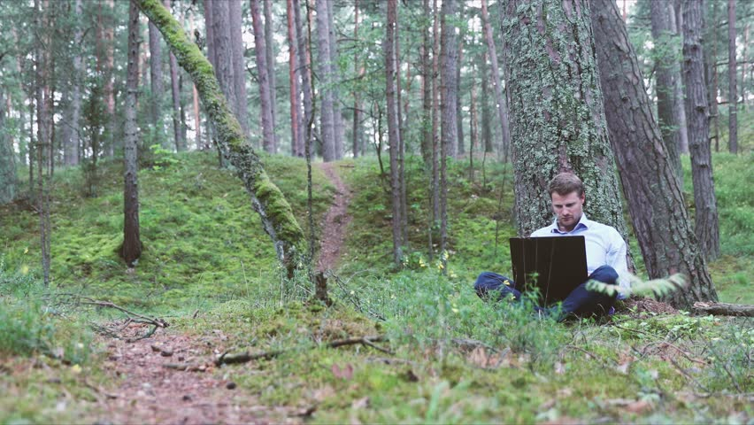 Young businessman working on laptop under the tree in the forest   Shutterstock HD Video #1013594108