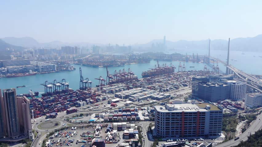 Container port and parking buildings, large storage of steel containers on land, aerial panoramic shot. Big bridge span across Rambler Channel, Hong Kong cityscape seen in fog far ahead