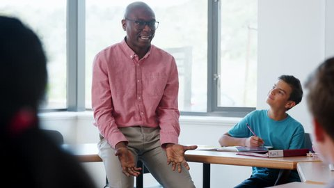High School Tutor Sitting On Desk And Teaching Class Shot In Slow Motion
