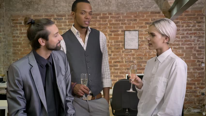Three multy-ethnic workers tell stories, joking, sitting in office, drinking champagne, communication concept | Shutterstock HD Video #1013617058