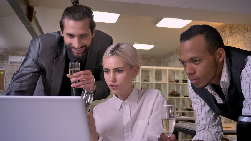 Three multy-ethnic workers are watching at screen of laptop, drink champagne, company party concept, communication concept | Shutterstock HD Video #1013617088