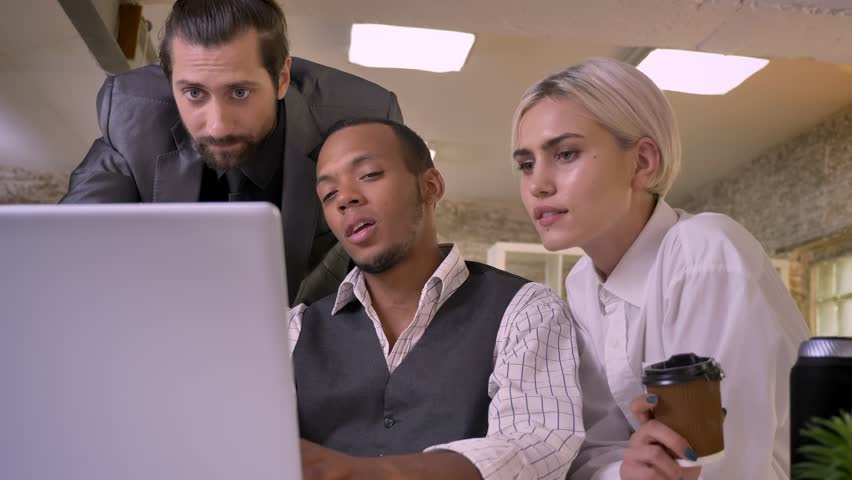 Three multy-ethnic workers discuss idea on laptop, laughing, coworking concept, communication concept | Shutterstock HD Video #1013617118