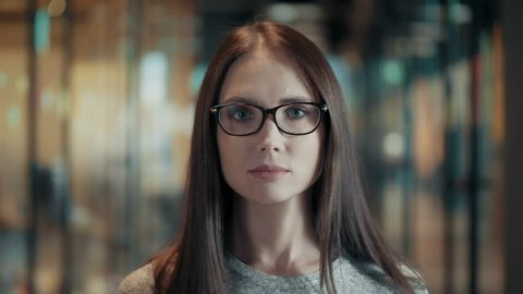 Portrait of tranquil peaceful young woman in glasses close up beautiful female brunette face calmly looking amazing businesswoman with long hair confident looking forward in modern start up office