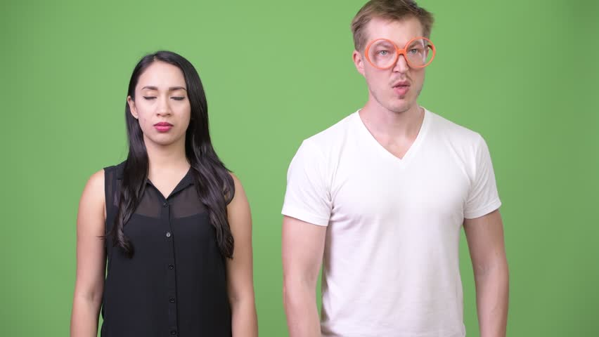 Young nerd man farting beside young Asian businesswoman