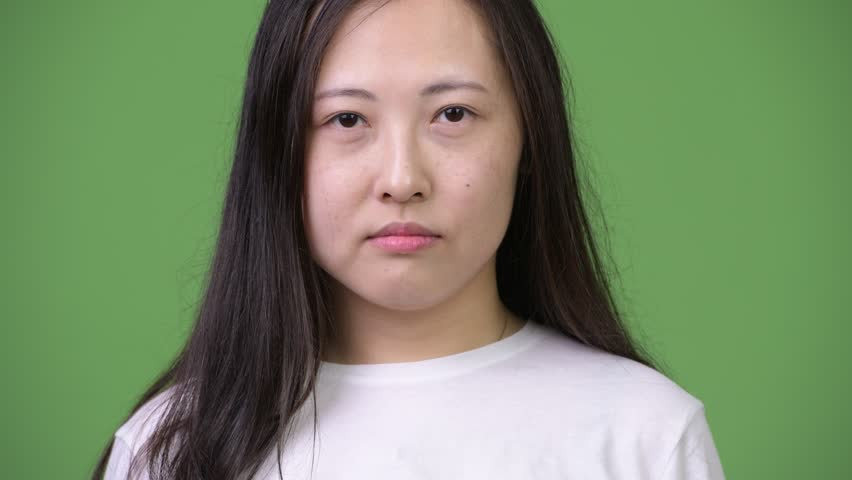 Young happy Asian woman smiling against green background | Shutterstock HD Video #1013619848