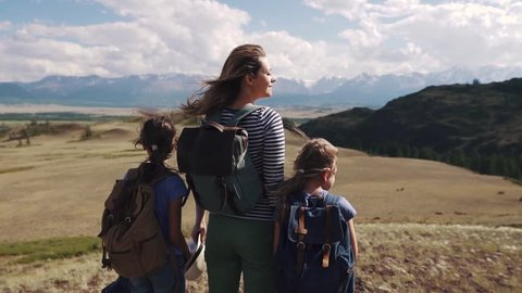 family of tourists on a journey. mother with two daughters in the campaign. children with backpacks admire the view of the mountains