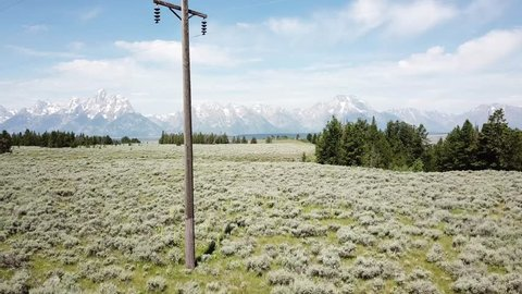 Telephone pole and Teton mountains aerial landscape in the summer western vista