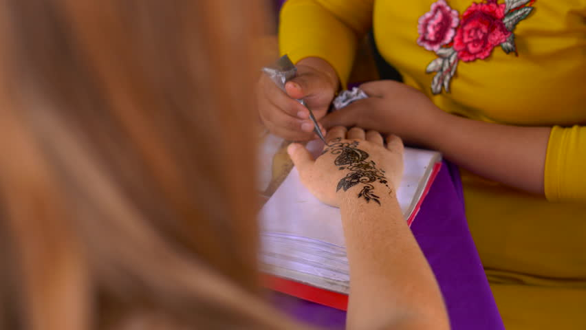 Young woman getting a temporary henna picture of a hindu pattern on a hand