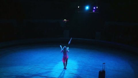 A woman juggles in the circus arena