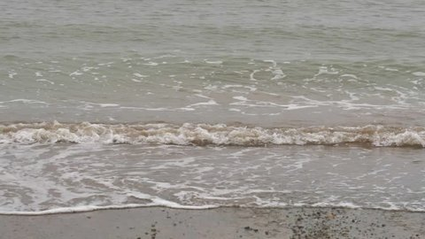 Mighty, wide sea water wave crushing and splashing on the sea bed, sea shore,ing the beach, it's sand and it's rocks with it. Filmed in slow motion and enhanced by a foggy, cloudy day.