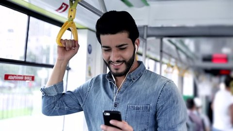 Bearded Young Attractive Man Chatting on his Smartphone. Standing in the Tram. Holding the Handrail. People in the Background. Man with Modern Wristwatch in Public Transport. Casual Outfit.