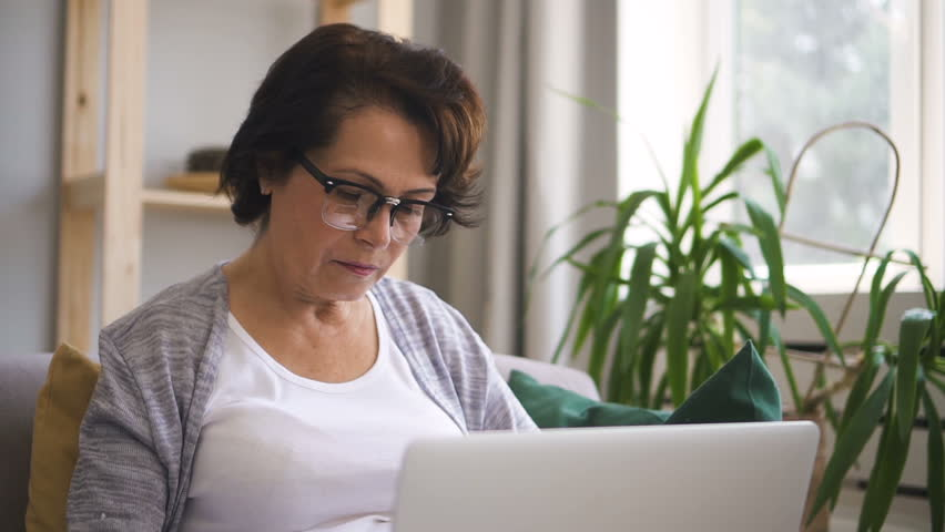 Mature woman with brown hair, in glasses is sitting at the sofa at home and woking on brand-new laptop. Indoors. Portrait. | Shutterstock HD Video #1013757128