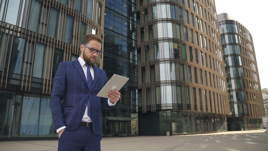Handsome businessman in blue suit working on brand-new tablet outside of modern business center. Outdoors. Portrait. | Shutterstock HD Video #1013757398