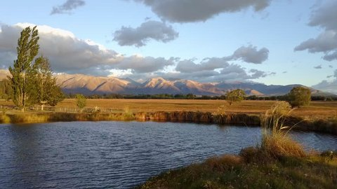 Aeria view of a pond with majestic New Zealand mountains in the background