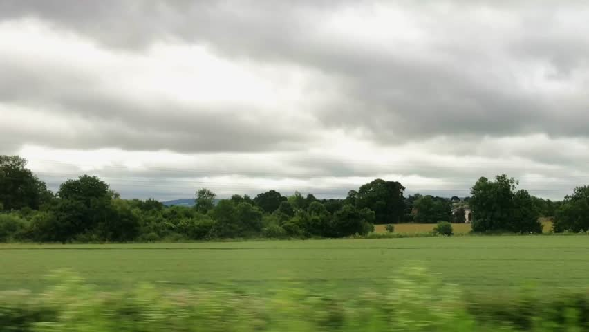 Wide shot out of a window of aing train, tracking along flat british countryside and farmland