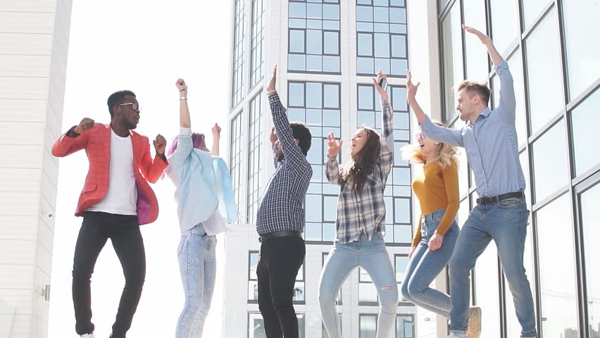 Multiracial heterosexual group of students having fun on roof party dancing and listening music at daytime on the roof area against glass office buildings background | Shutterstock HD Video #1013800028