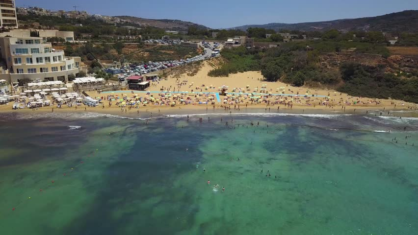 Ghajn Tuffieha, Malta - 4K flying above beautiful Golden Bay beach on a summer morning with tourists and crystal clear sea water