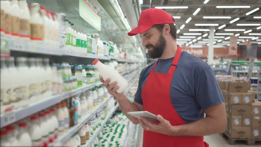 Handsome male merchandiser checking milk products with digital tablet | Shutterstock HD Video #1013816438
