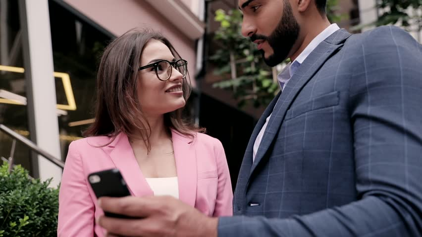 Close up view Couple of Succeessful Collegues. Businessman and Businesswoman Looking at Smartphone. Talking about Deal. Classical Suits. Smiling Happily. Meeting of two Business Partners.   Shutterstock HD Video #1013836778