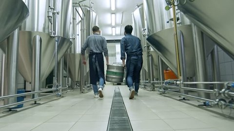 Close-up shot of two brewery workers lifting up beer keg together and walking away from the camera through brewhouse