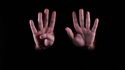 Hand gestures coming out of the dark into the light. The number nine.