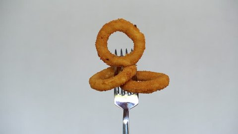 Squid rings on the fork. Rings of onions or squid in breading, rotate against a light background.