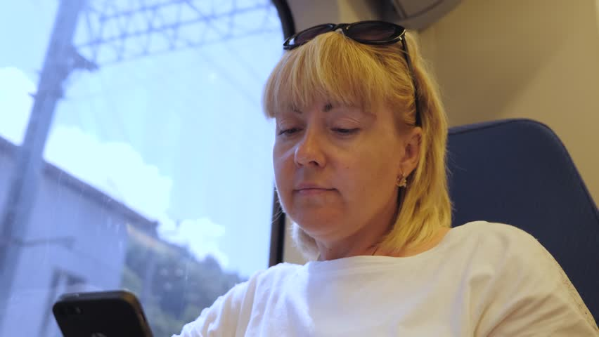 Young beautiful woman tourist traveling by train, sitting next to a window, using a smartphone. The concept of travel | Shutterstock HD Video #1013859818