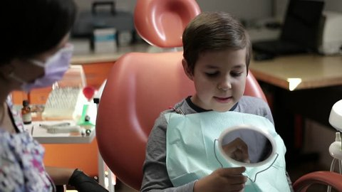 medicine, dentistry and healthcare concept - female dentist with kid patient at dental clinic adjusting chair