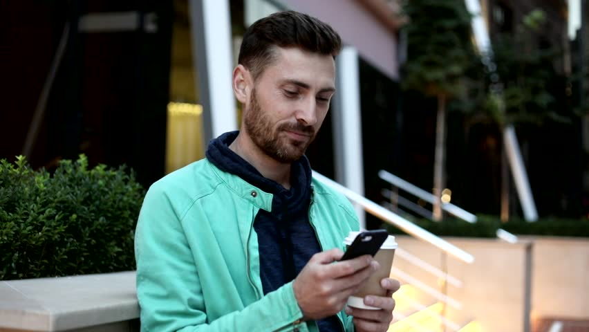 Sincerly Smiling Young Man Standing by the Modern Building. Chatting on the Mobile Phone. Using it. Holding a Paper Cup with Coffee. Casually Dressed. Pleasant Mood. Big City. Glass Building. | Shutterstock HD Video #1013876858