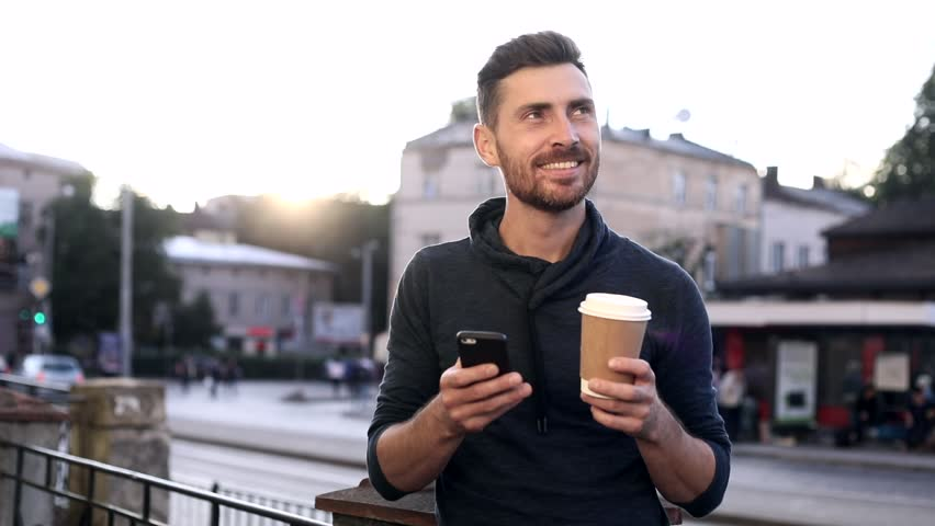 Close up of Handsome Man Standing in the Town. Holding a Paper Cup with Black Coffee. Using her Modern Smartphone. Reading a Message. Crowded Bus Stop on the Background. | Shutterstock HD Video #1013880368